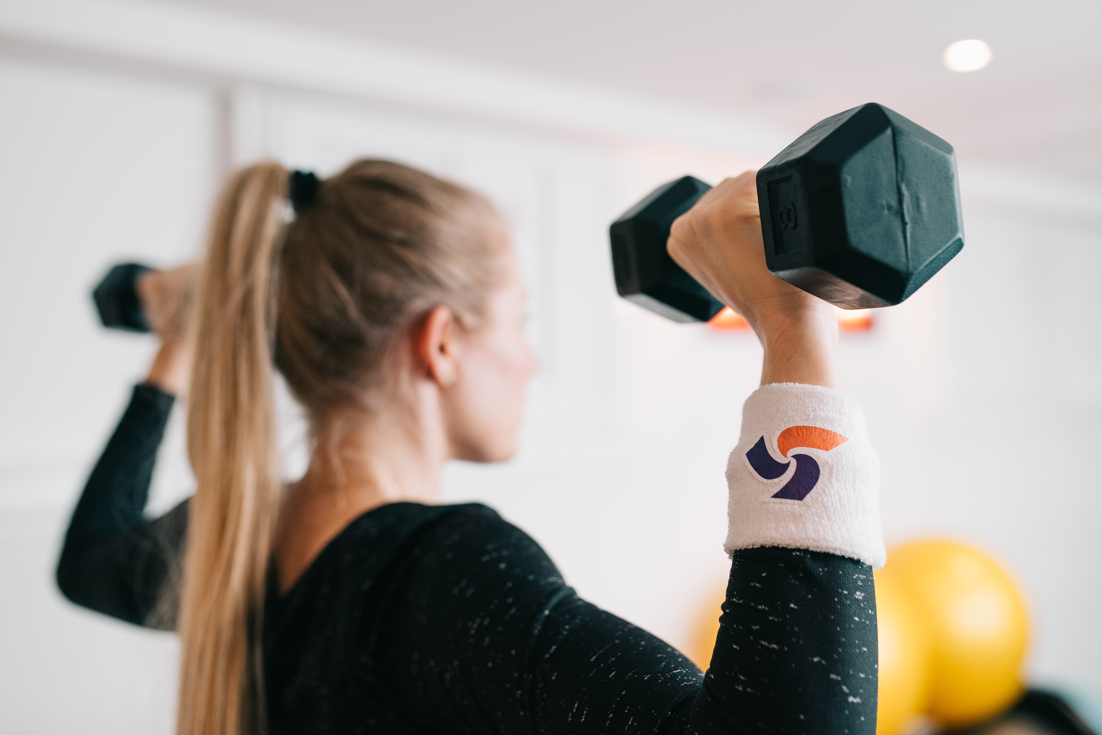 woman lifting weights with PAC wristband on