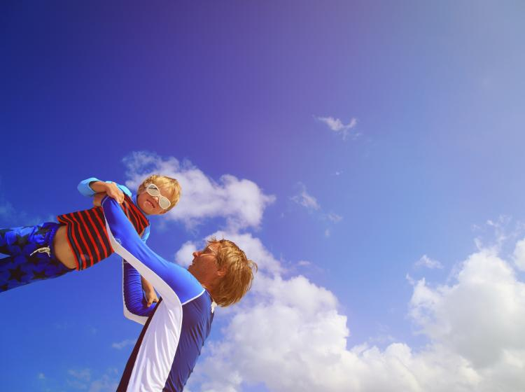 Father throwing son in the air, in front of blue sky