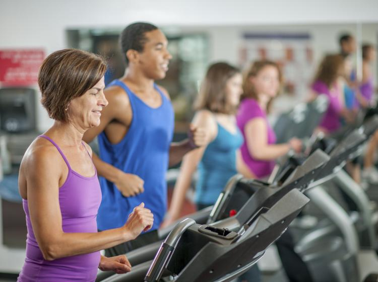 Group of people walking on treadmills at the gym, smiling