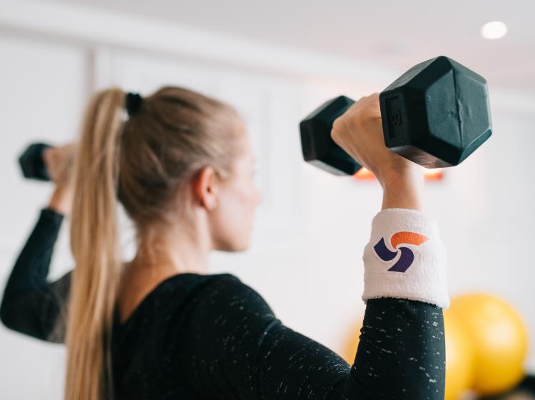 woman lifting weights with ParticipACTION wristband