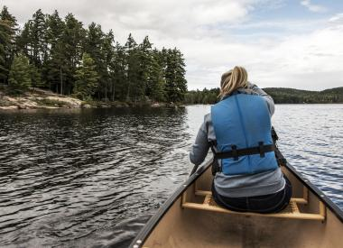 Girl paddles a canoe wearing a life jacket