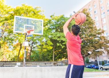 Man shooting a basketball in an outdoor court