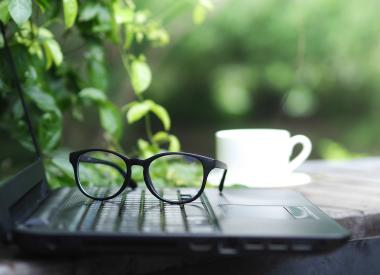 Laptop, eye glasses, and a cup of coffee in an outdoor workspace