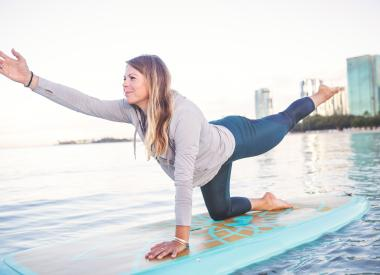 Woman does yoga on a stand-up paddleboard