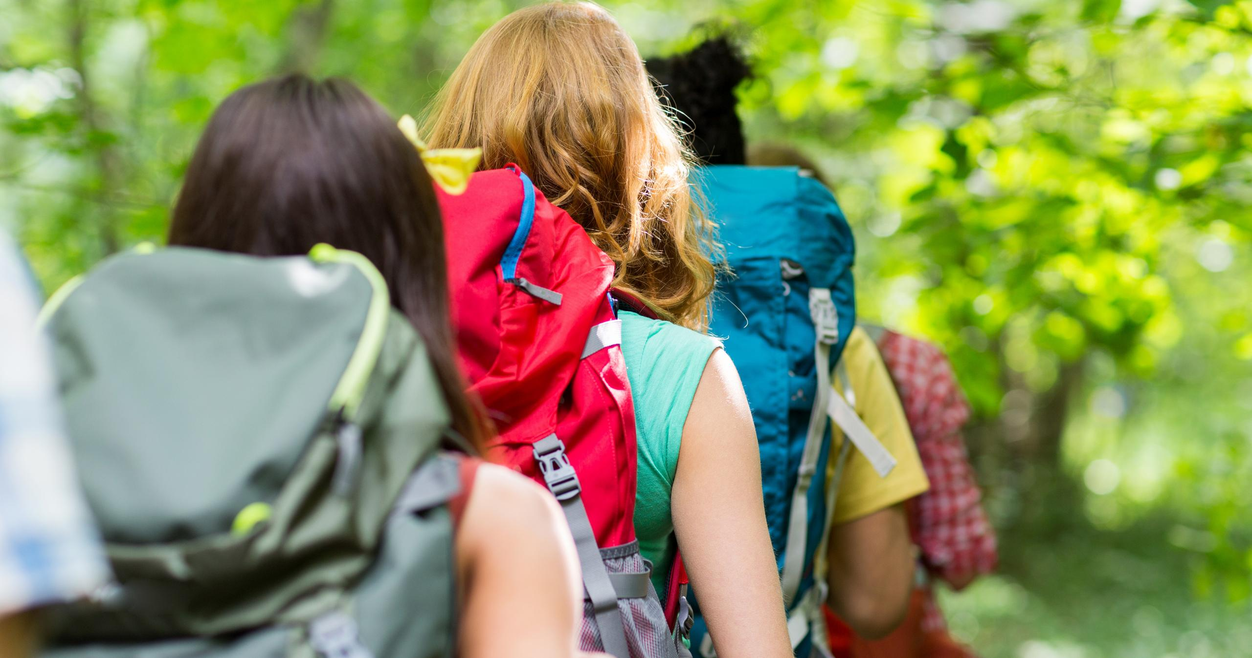 teens hiking with back through forest